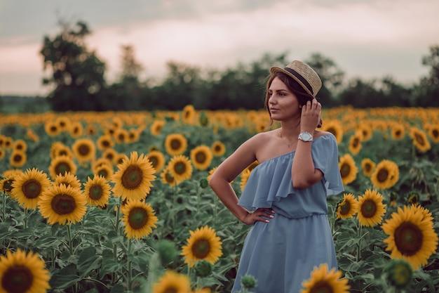 Träumende junge frau im blauen kleid und im hut, die haare mit einer hand in einem feld von sonnenblumen im sommer, vorderansicht halten. zur seite schauen. speicherplatz kopieren