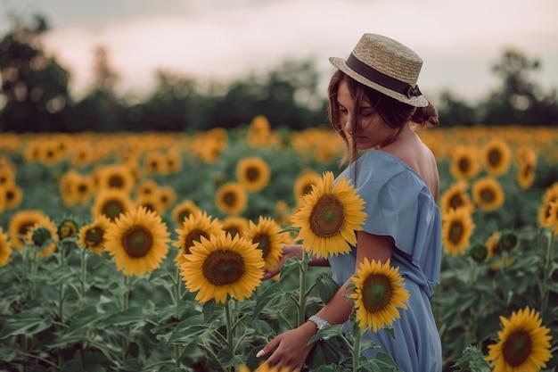 Träumende junge frau im blauen kleid und im hut, die sonnenblume mit einer hand in einem feld von sonnenblumen im sommer halten, blick von ihrer seite. herunterschauen. speicherplatz kopieren