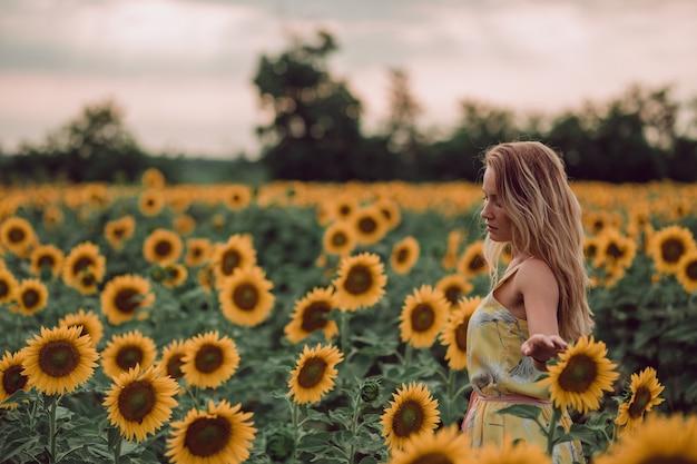 Träumende junge frau im gelben kleid, das blumen mit den händen in einem feld der sonnenblumen im sommer hält, blick von ihrem rücken. zur seite schauen. speicherplatz kopieren