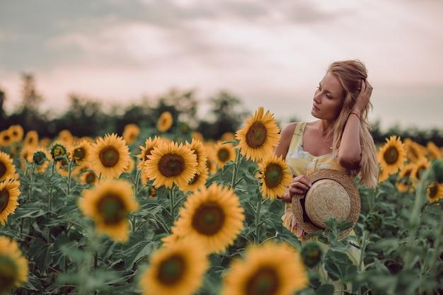 Träumende junge frau im gelben kleid, das haare und hut mit händen in einem feld von sonnenblumen im sommer hält, blick von ihrer seite. zur seite schauen. speicherplatz kopieren