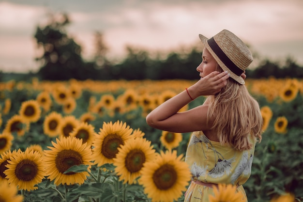 Träumende junge frau im gelben kleid, das haare und hut mit hand in einem feld von sonnenblumen im sommer hält, blick von ihrer seite. zur seite schauen. speicherplatz kopieren