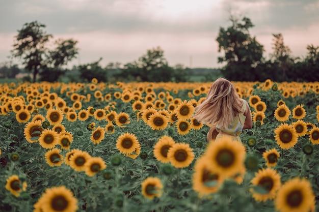 Träumende junge frau im gelben kleid, das ihren kopf mit den haaren in einem feld der sonnenblumen im sommer winkt, blick von ihrer seite. blick auf den seitlichen kopierraum