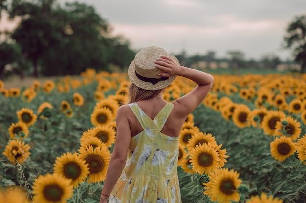 Träumende junge frau im gelben kleid, die einen hut mit einer hand hält und im sommer in einem feld von sonnenblumen weggeht, blick von ihrem rücken. ich freue mich auf. speicherplatz kopieren