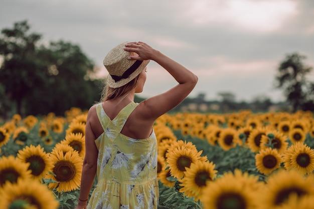 Träumende junge frau im gelben kleid, die einen hut mit einer hand hält und im sommer in einem feld von sonnenblumen weggeht, blick von ihrem rücken. zur seite schauen. speicherplatz kopieren