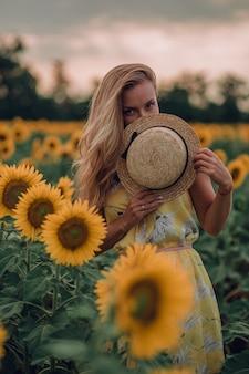 Träumende junge frau im gelben kleid versteckt ihre augen mit einem hut in einem feld von sonnenblumen im sommer, blick von ihrer vorderseite. nach vorne schauen. speicherplatz kopieren