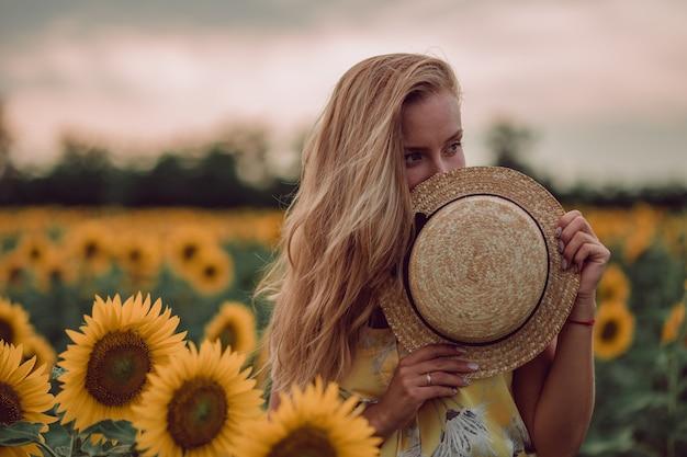 Träumende junge frau im gelben kleid versteckt ihre augen mit einem hut in einem feld von sonnenblumen im sommer, blick von ihrer vorderseite. zur seite schauen. speicherplatz kopieren
