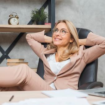 Träumende junge geschäftsfrau, die auf stuhl im büro sich entspannt