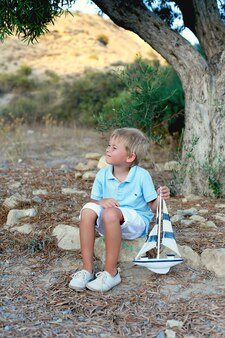 Träumender junge, der unter einem baum sitzt und spielzeugboot hält