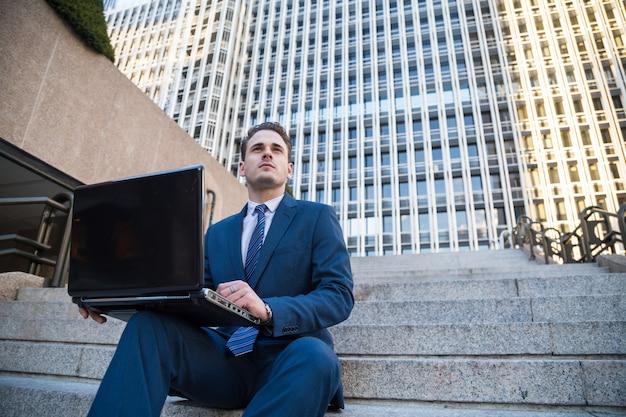 Träumender mann in der eleganten klage, die auf treppe mit laptop auf den knien weg schauen aufwirft.