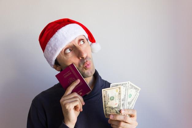 Träumer mann auf weihnachtsmütze mit reisepass und dollarnoten mit nachdenklichem blick weihnachtsferien