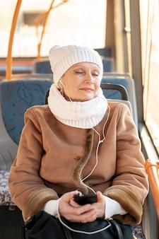 Träumerische ältere hörende musik der frau
