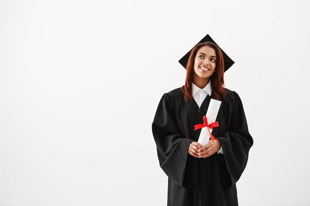 Träumerische afrikanische frau graduiert lächelnd und hält diplom.