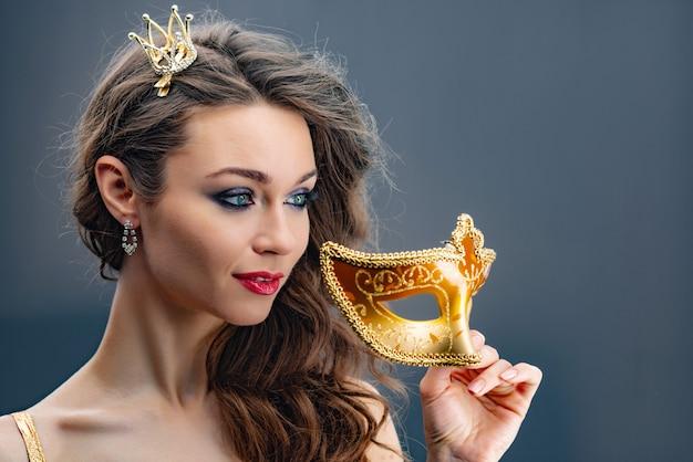Träumerische frau, die weg mit einer prinzessinkrone auf ihrem kopf schaut und hält eine goldene nahaufnahme der karnevalsmaske in der hand