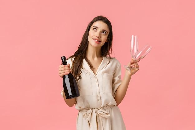 Träumerische und romantische junge schöne frau, die valentinstag-datum plant, nachdenklich stehend schaut und perfekte hochzeit darstellt, champagner und zwei gläser hält und sinnlich lächelt