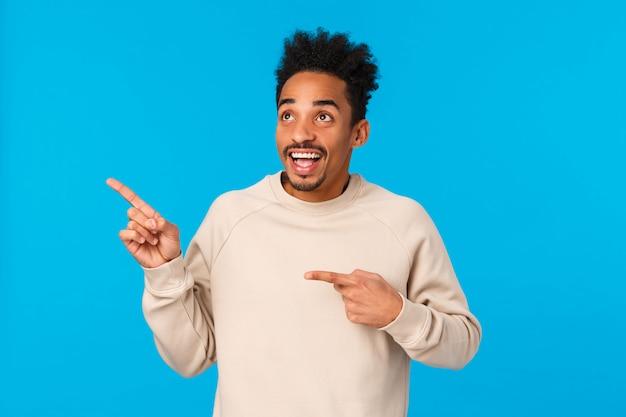 Träumerischer inspirierter und unterhaltener, aufgeregter lächelnder afroamerikanermann, der den ersten schnee sieht, produkt, firmenfahne betrachtet, die obere linke ecke fasziniert, blau anstarrt und zeigt