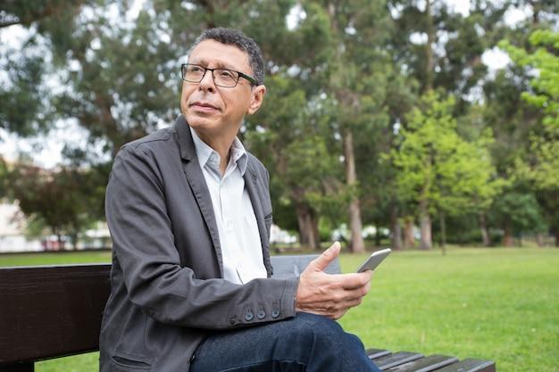 Träumerischer mann, der smartphone verwendet und auf bank im park sitzt
