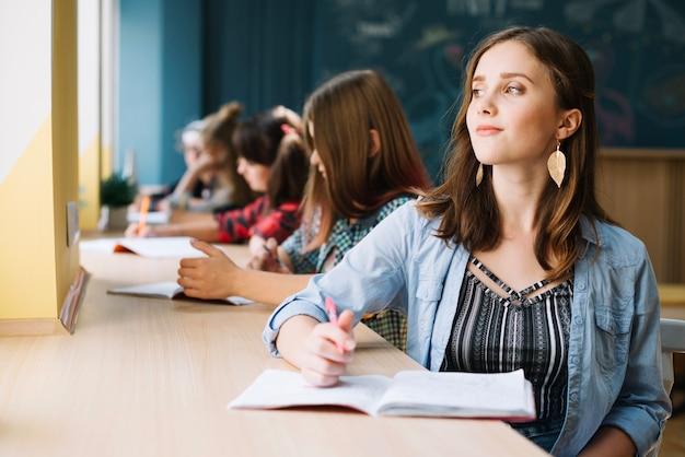 Träumerischer student am schreibtisch