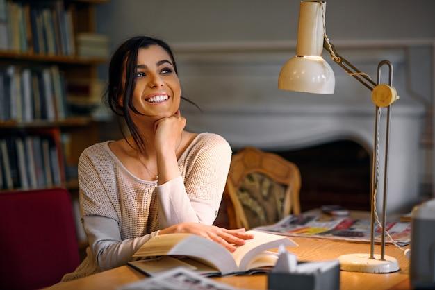 Träumerisches hübsches und enthusiastisches studentenmädchen mit perfektem lächelnlesebuch in der universitätsbibliothek unter einer tischlampe