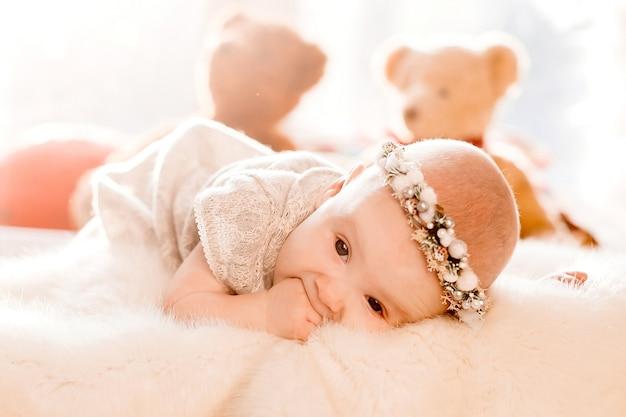 Träumerisches kleines mädchen liegt auf flaumiger decke in einem bett