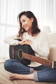 Träumerisches mädchen, das gitarre spielend genießt