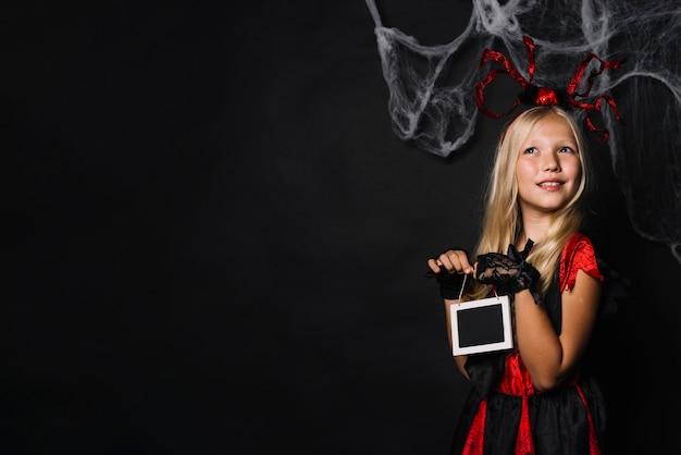 Träumerisches mädchen in halloween-kostüm, das tafel hält