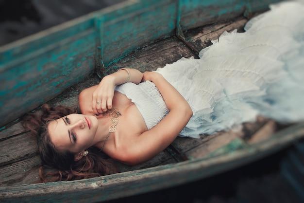 Träumerisches mysteriöses blondes mädchen in einem weißen kleid in einem alten boot auf dem see