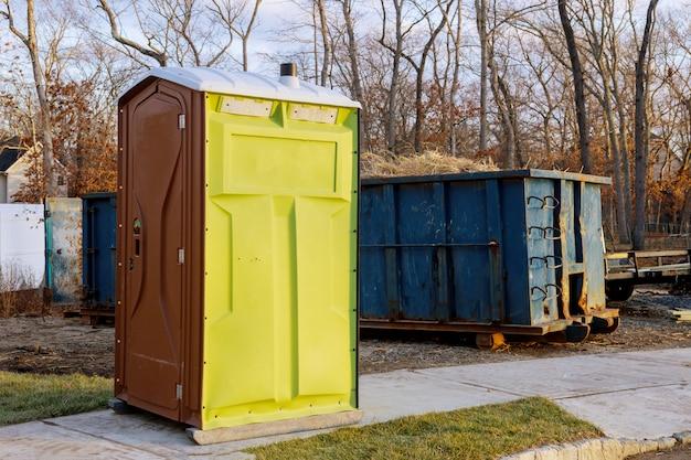 Tragbare chemische toiletten für den bau eines neuen hauses und müllcontainers voller müll