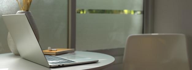 Tragbarer arbeitsbereich mit laptop, schreibwaren und zubehör auf weißem kreistisch neben dem fenster