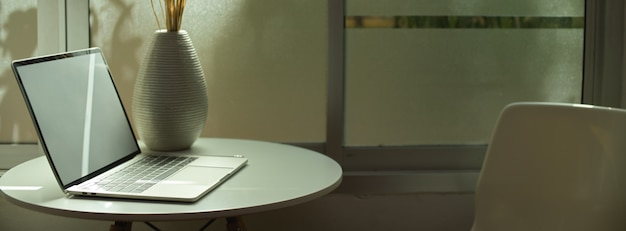 Tragbarer arbeitsbereich mit laptop und dekoration auf weißem kreistisch neben dem fenster