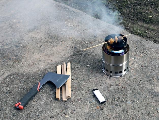 Tragbarer holzofen räuchert fleisch auf einem holzstab