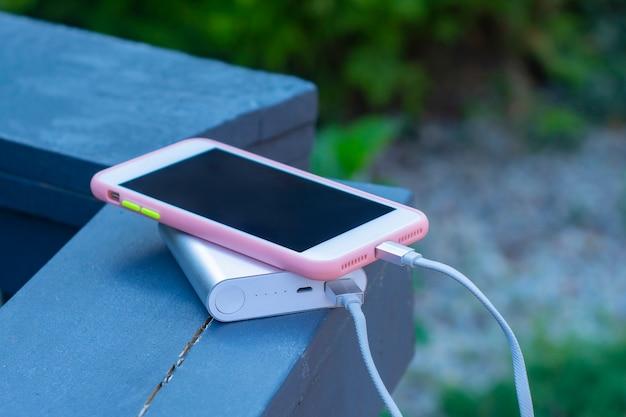 Tragbares ladegerät lädt ein smartphone auf einem holzgeländer. handymodell mit dunklem bildschirm und powerbank.