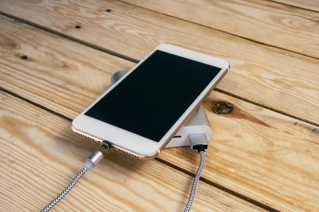 Tragbares ladegerät lädt ein smartphone auf einem holztisch. handymodell mit dunklem bildschirm und powerbank.