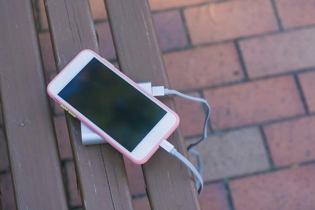 Tragbares ladegerät lädt ein smartphone auf einer holzbank. handymodell mit dunklem bildschirm und powerbank.