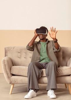 Tragen eines virtual-reality-headsets und sitzen auf der couch