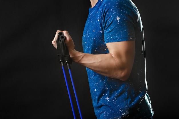 Tragen sie ein teil des männlichen körpers, blaues t-shirt mit fitnessgeräten in der rechten hand