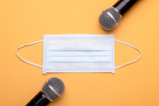 Tragen sie immer noch eine maske, während sie sprechen. draufsicht neues vorbeugendes gesicht mak und schwarzes drahtloses mikrofon.