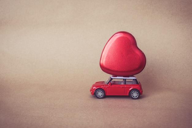 Tragen sie liebesvalentinstag: miniaturrotauto, das ein rotes herz trägt