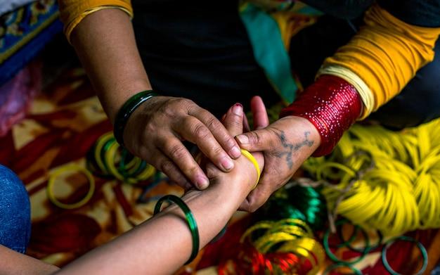 Tragen von armreifen zur hand während des nepalesischen festivals ab kathmandu, nepal.