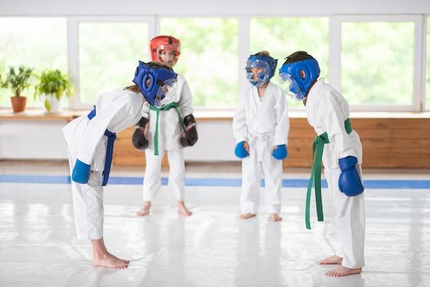 Tragen von schutzhelmen. jungen und mädchen tragen schutzhelme und boxhandschuhe beim gemeinsamen üben