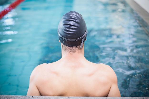 Tragende badekappe und schutzbrillen des gutaussehenden mannes am pool