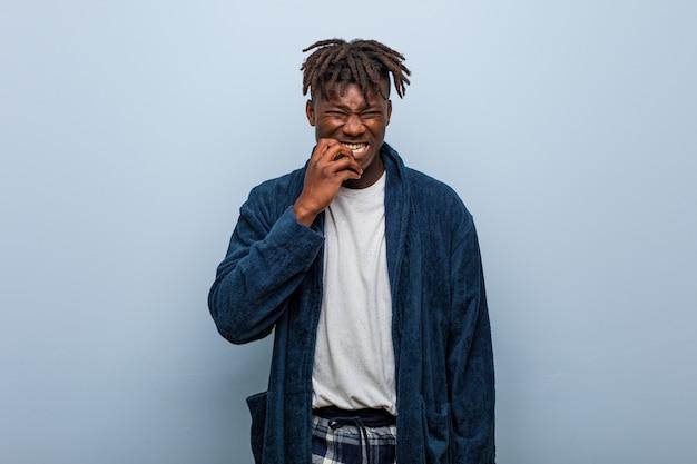 Tragende beißende fingernägel des pyjamas des jungen afrikanischen schwarzen mannes, nervös und sehr besorgt.