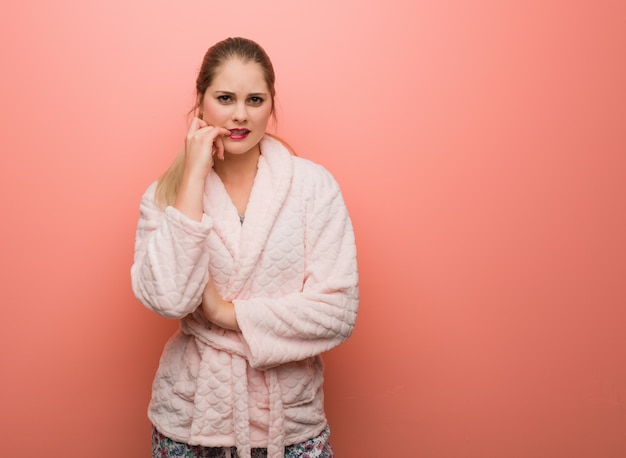 Tragende beißende nägel des pyjamas der jungen russischen frau, nervös und sehr besorgt