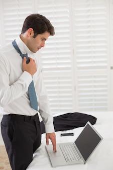 Tragende bindung des geschäftsmannes bei der anwendung des laptops an einem hotelzimmer
