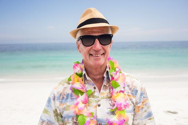 Tragende blumengirlande des glücklichen älteren mannes auf dem strand