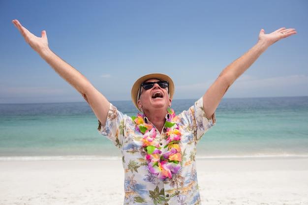 Tragende blumengirlande des glücklichen älteren mannes und genießen auf dem strand
