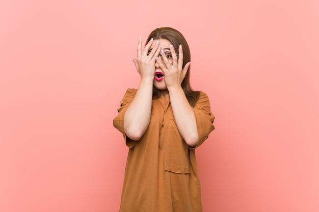 Tragende brillen der jungen studentenfrau blinken durch die erschrockenen und nervösen finger.