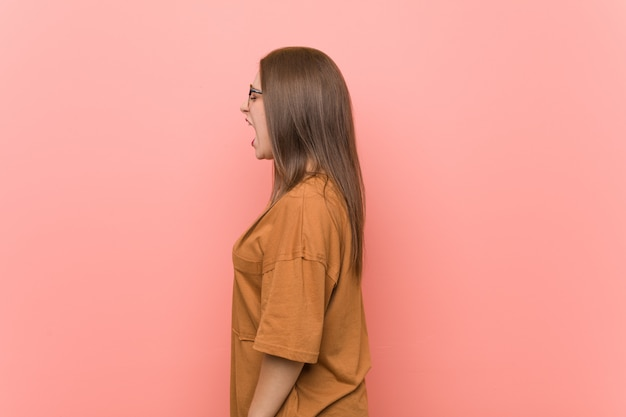 Tragende brillen der jungen studentenfrau, die in richtung zu einem kopienraum schreien
