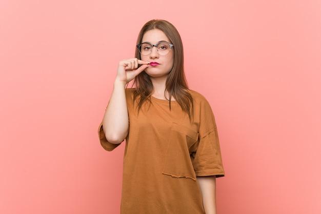 Tragende brillen der jungen studentenfrau mit den fingern auf den lippen, die ein geheimnis halten.