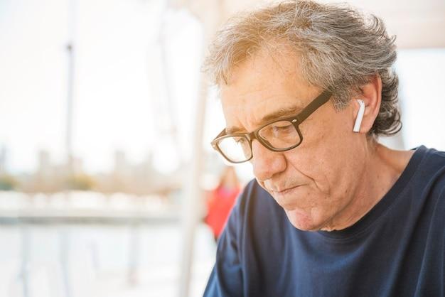 Tragende brillen des älteren mannes mit weißem bluetooth kopfhörer in seinem ohr