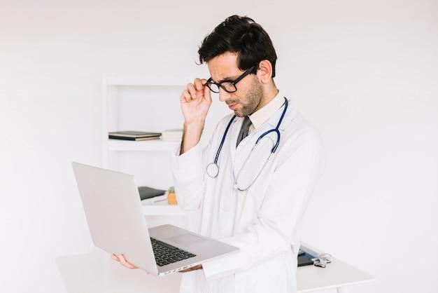 Tragende brillen des jungen männlichen doktors, die laptopbildschirm betrachten